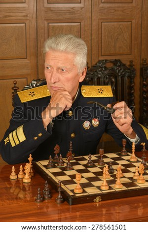 Military mature general at the table playing chess - stock photo