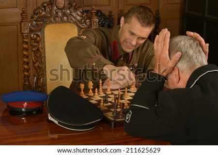 Military mature general on the table playing chess with soldier - stock photo