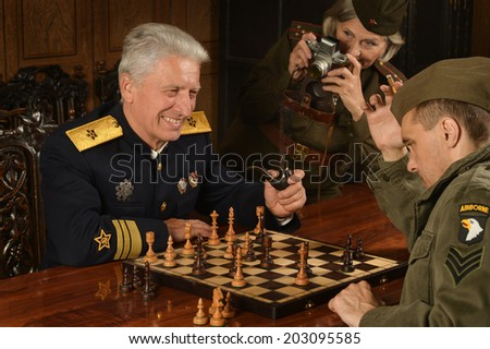 Military mature general on the table with soldiers playing chess - stock photo