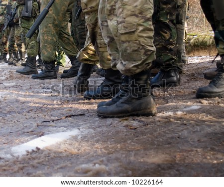 Military men standing in line with their boots in mud