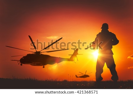 Military Mission at Sunset. Marines Helicopters Air Mission. Soldier with Assault Rifle Cover the Area. - stock photo