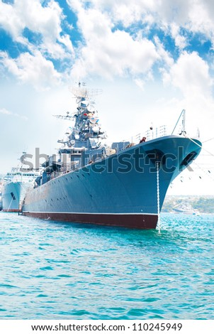 Military navy ship in the bay against blue sky - stock photo