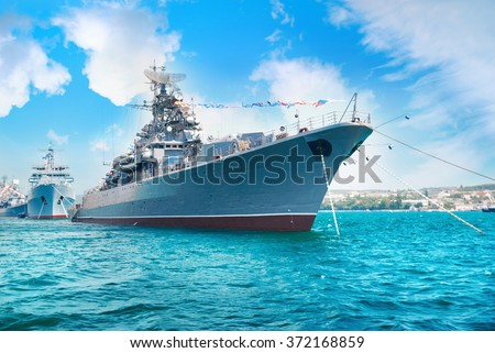 Military navy ship in the bay. Military sea landscape with blue sky and clouds - stock photo