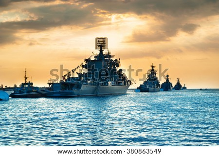 Military navy ships in a sea bay at sunset time - stock photo