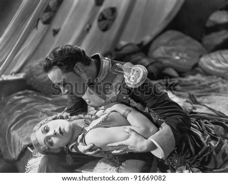 Military officer holding swooning woman - stock photo