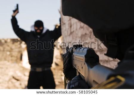 Military policeman taking armed criminal under arrest - stock photo