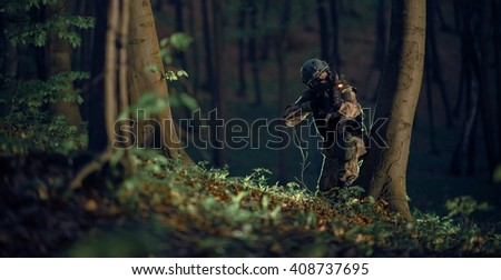 Military Soldier in Action at Night in the Forest Area. Night Time Military Mission. Panoramic Photo. Soldier with Assault Rifle with Flashlight Between Trees. - stock photo