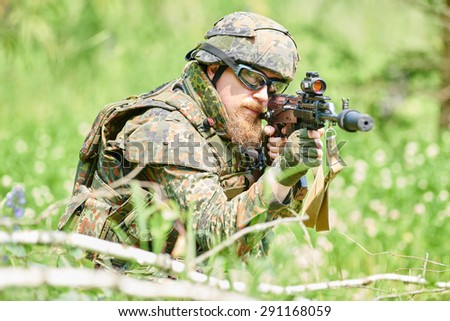 military. soldier targeting  with assault rifle at position in nato germany uniform outdoors - stock photo