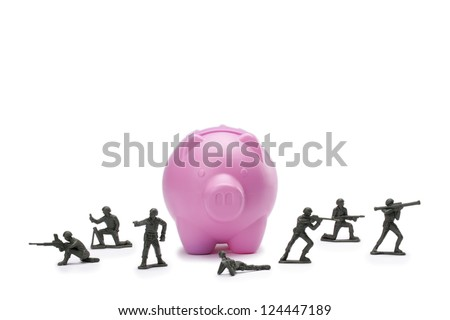 Military soldier with rifles and ready to protect the piggy bank against white background - stock photo