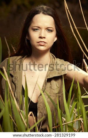Military style beauty posing for portrait in wild nature - stock photo