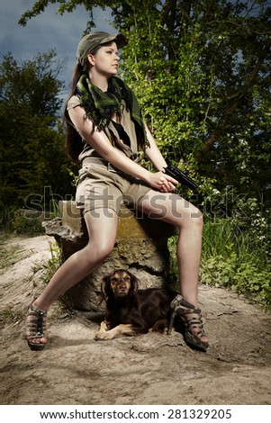 Military style pretty lady posing with pistol in wild nature - stock photo