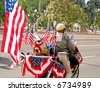 Military Veteran with Decorated Motorcycle in Parade - stock photo