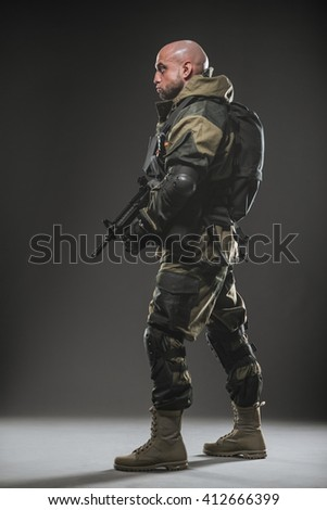 Military, war, conflict, soldiers - Special forces soldier man hold Machine gun on a  dark background. Military equipment of Russian soldiers