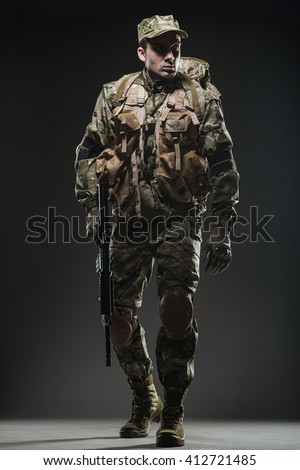 Military, war, conflict, soldiers - Special forces soldier man hold Machine gun on a  dark background. Military equipment NATO soldiers - stock photo