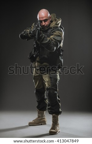 Military, war, conflict, soldiers - Special forces soldier man hold Machine gun on a  dark background. Soldier takes aim.  Military equipment of Russian soldiers