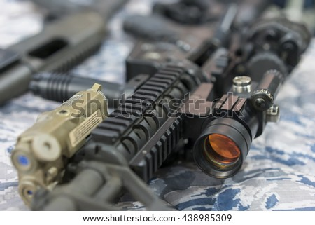 Military weapon laying on camouflage - stock photo