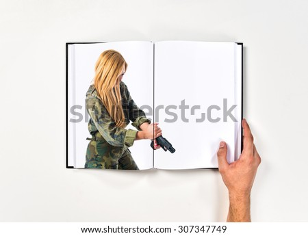 Military woman carrying a gun printed on book - stock photo