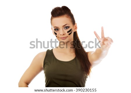 Military woman gesturing peace with fingers - stock photo