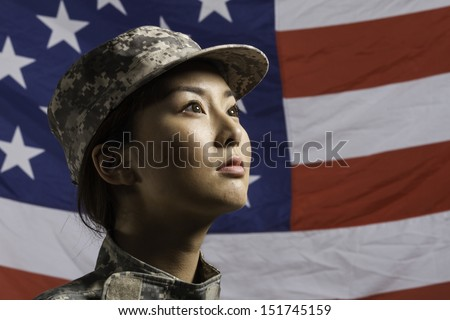 Military woman in front of US flag, horizontal - stock photo