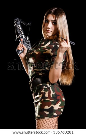 Military woman loading the arbalest over black background - stock photo