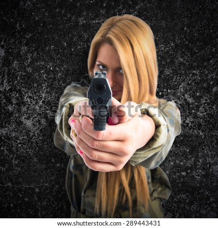 Military woman with gun over textured background - stock photo