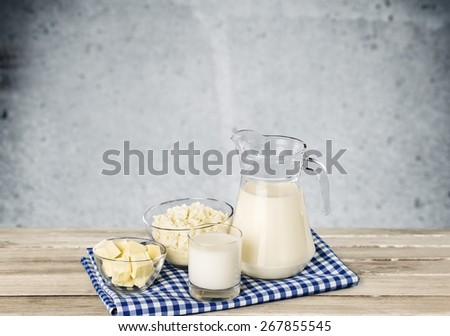Milk. A glass of milk and a milk jug on plaid tablecloth. - stock photo