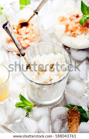 Milk and cardamon, lemon and black tea granita in glasses on a vintage metal tray with ice cubes with fresh mint leaves