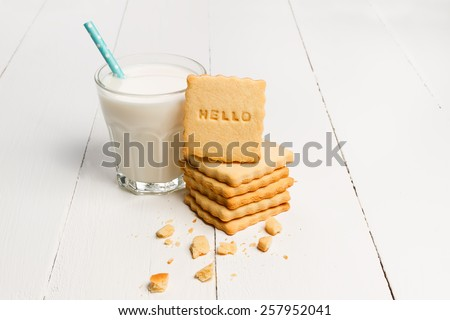 Milk and cookie with HELLO sign against white wooden background  - stock photo