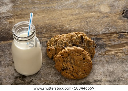 Milk and cookies childhood treat set out on an old rustic wooden table with a glass bottle of fresh milk with a straw and a pile of crunchy cookies, high angle with copyspace - stock photo