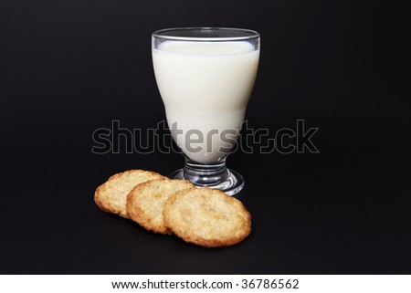Milk and cookies on black background