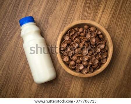 milk and cornflakes in wood bowl on a wooden table background. Organic healthy food rich in minerals and vitamins. Eco food for breakfast. - stock photo