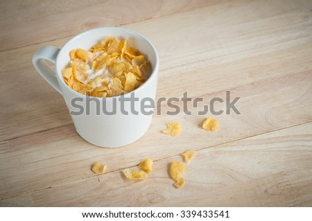 milk and fresh cereal cornflakes in white cup that ready for breakfast - stock photo