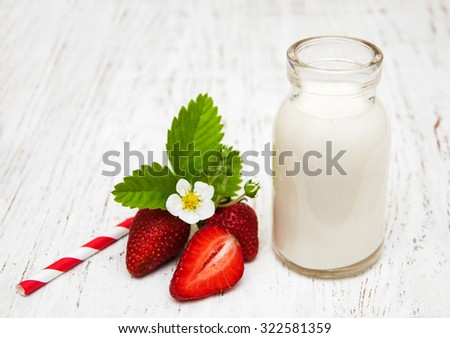 Milk and strawberries on a wooden background - stock photo