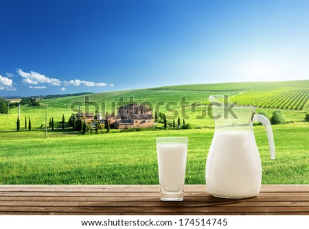 milk and sunny spring field - stock photo
