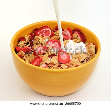 Milk being poured on a bowl of corn flakes with strawberry flakes - stock photo