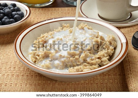 Milk being poured on a bowl of oatmeal - stock photo