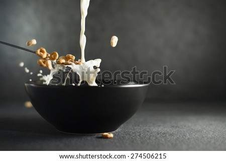 Milk being poured on ring cereals in spoon over dark bowl on dark background - stock photo