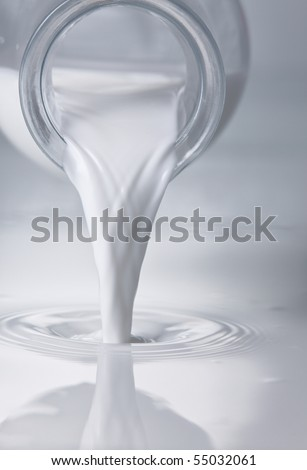 Milk being poured onto a container. - stock photo