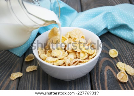 milk being poured over a bowl full of  cereal  - stock photo