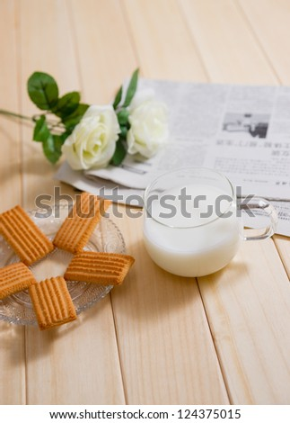 milk,biscuit and newspaper on a table at breakfast