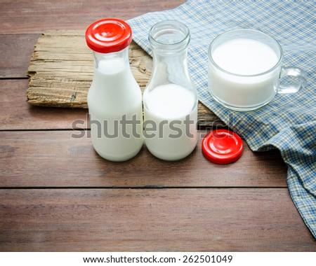 Milk bottle and milk glass put on wooden. - stock photo