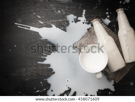 Milk bottle and Milk spilled on dark wood,top view