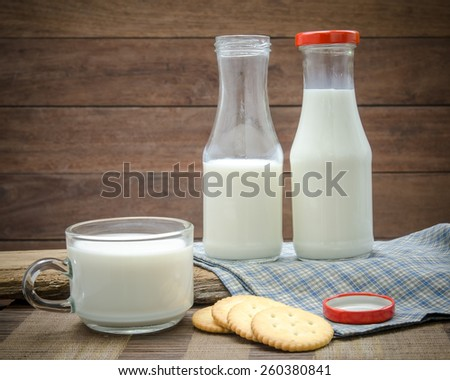 Milk bottle, milk glass and cookie put on wooden. - stock photo