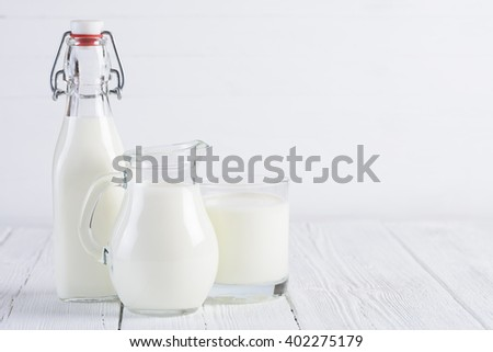 Milk bottle with jug and glass of milk on white wooden table - stock photo