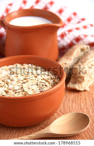 Milk, bread and cereals on a wooden background.