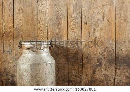 Milk can on wood vintage background - stock photo