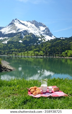 Milk, cheese and bread served at a picnic in an Alpine meadow, Switzerland - stock photo