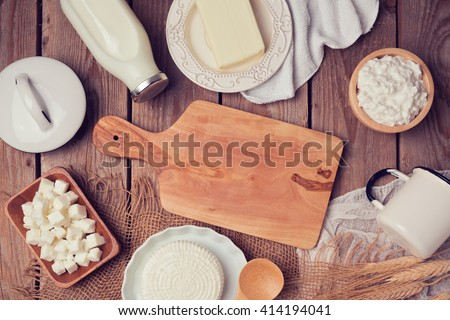 Milk, cheese and butter with cutting board on wooden background. View from above. Flat lay - stock photo