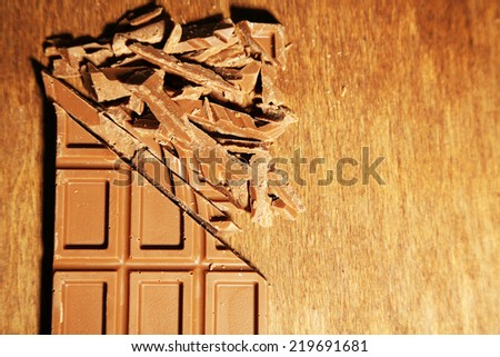 Milk chocolate bar on color wooden background - stock photo