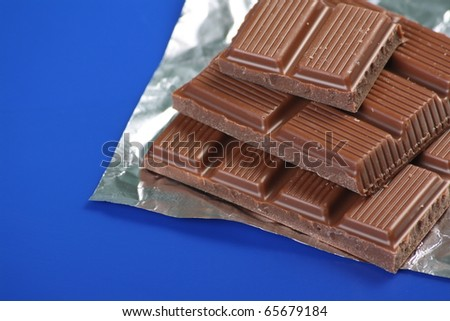 Milk Chocolate pieces or squares and a foil wrapper on a blue background with copy space